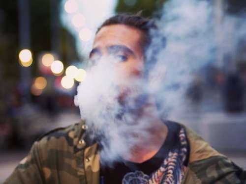 man smoking street city bokeh