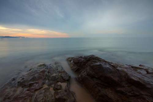 sea water rocks horizon clouds