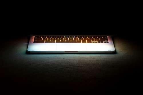 laptop keyboard glow black background copy space