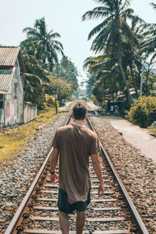 man walking tracks train transport