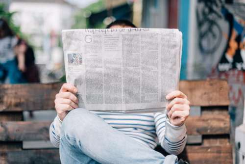 people man reading newspaper sitting