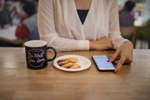 woman cafe phone browsing snack