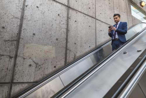 busy businessman escalator mobile phone