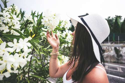 woman smelling flowers nature hat
