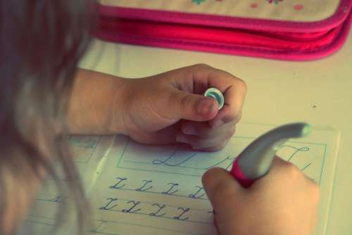 child kid writing homework letters