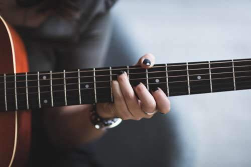 woman playing guitar nails female