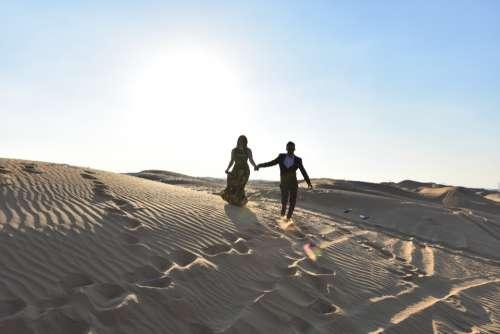 couple walking sand desert sand dune