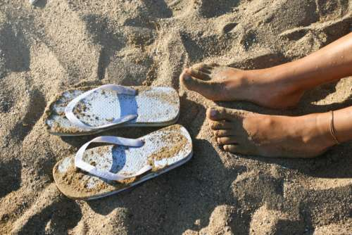 female feet flip-flop beach sand