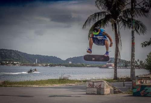 skateboarder jump flip tank top sunset