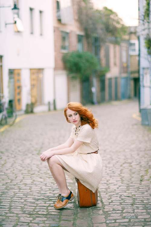fashion model sitting suitcase street