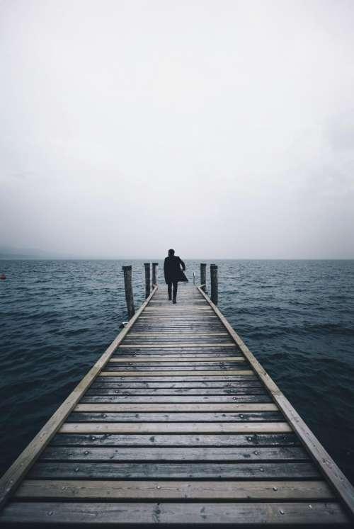 people man bridge water ocean