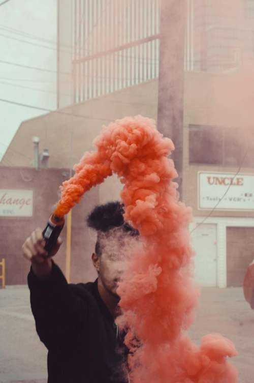 people man smoke bomb orange
