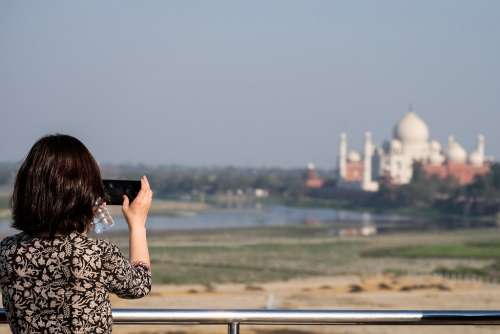 Tourist Girl Taking Pictures of Taj Mahal