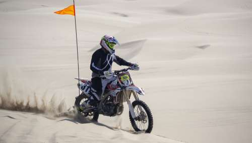 A Dirt Bike Racer Spins Sand Riding Over Dunes Photo