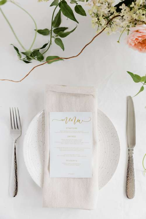 A Linen Napkin Topped With A Gold-Lettered Menu Photo