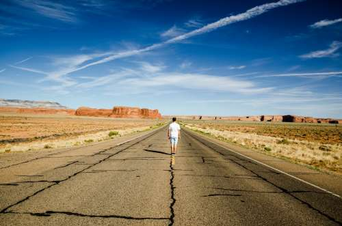 A Man Stands On The Road Markings Of A Desert Highway Photo