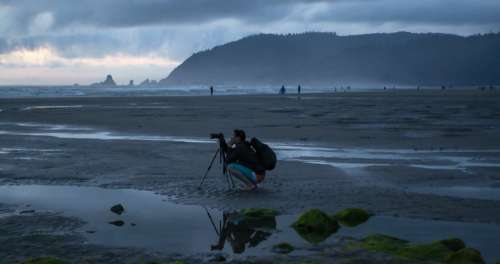 A Photographer Crouches At His Tripod On A Misty Beach Photo