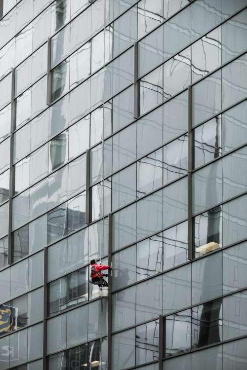A Window Washer Dangles From A Skyscraper Photo