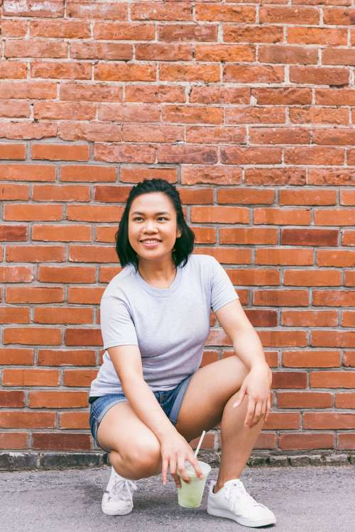 Crouching In Front Of Brick Wall Photo