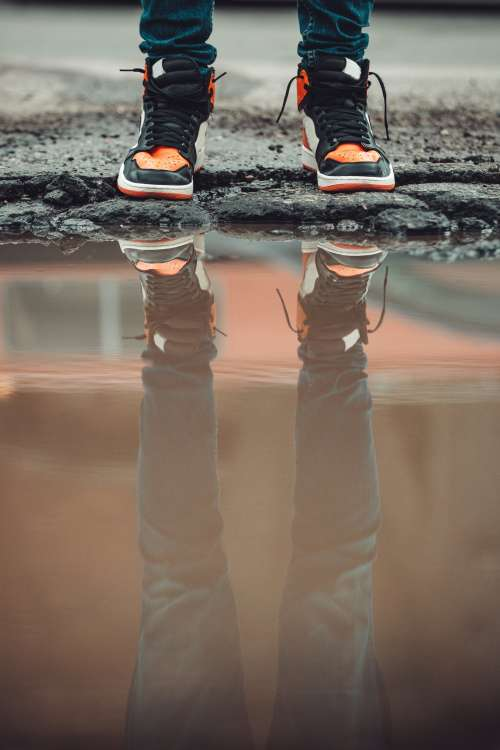 Dark Denim Jeans And Fashion Sneakers Reflect In City Puddle Photo