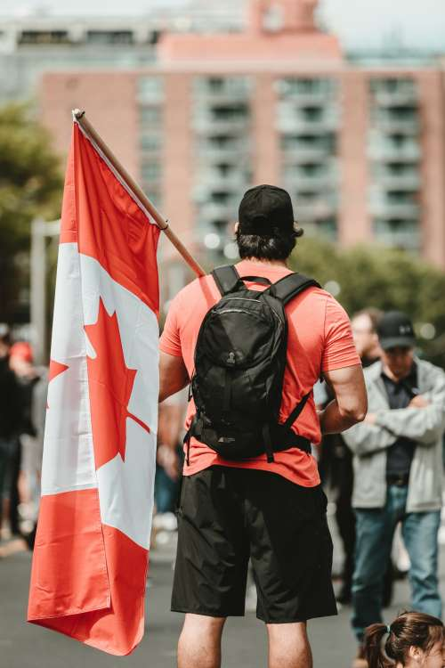 Man In A Crown Holding A Canadian Flag Photo