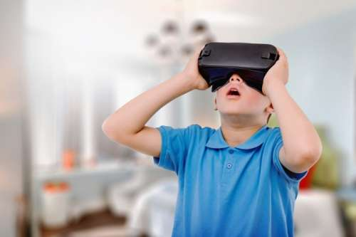 Amazed teen boy wearing virtual reality goggles watching movies or playing video games.