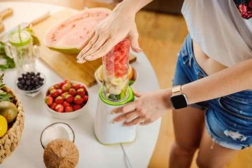 Hands of woman preparing smoothie fruit drink