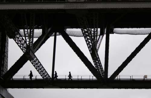 people crossing bridge monochromatic silhouette