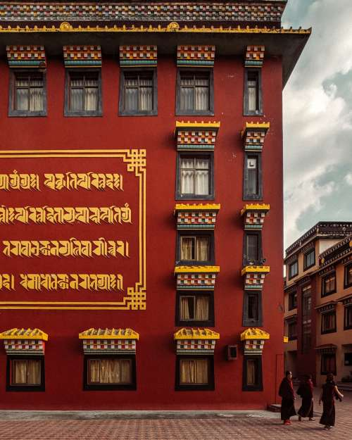A Crimson Building With Gold Writing On The Walls Photo