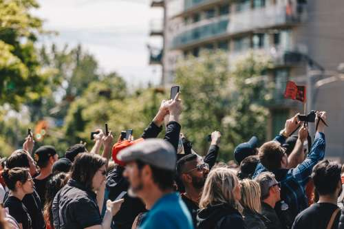 A Crowd Holds Up Their Phones In The Sun Photo