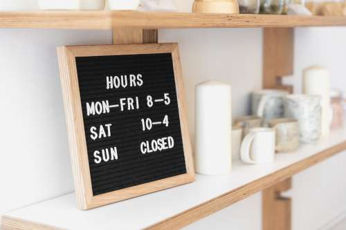 A Letter Board Displays Opening Times On A Shop Shelf Photo
