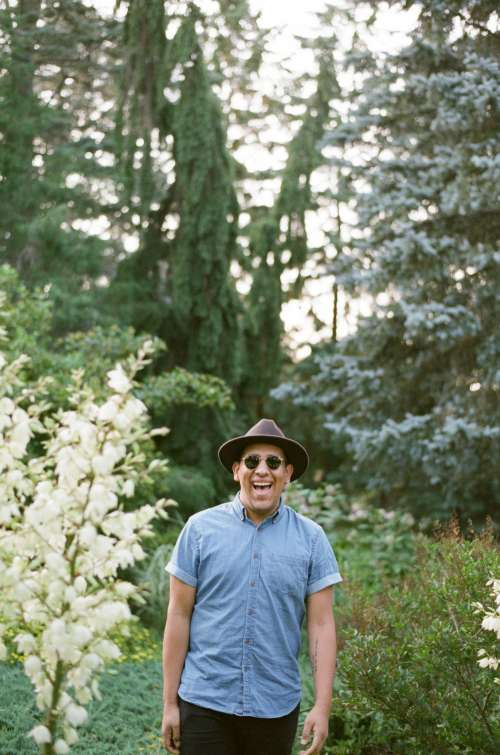 A Man in A Fedora And Sunglasses Beams In The Woods Photo