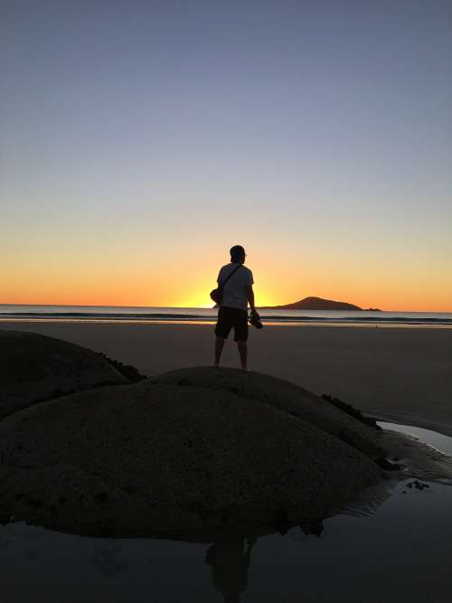 A Man On A Dune Watches The Sun Set From The Beach Photo