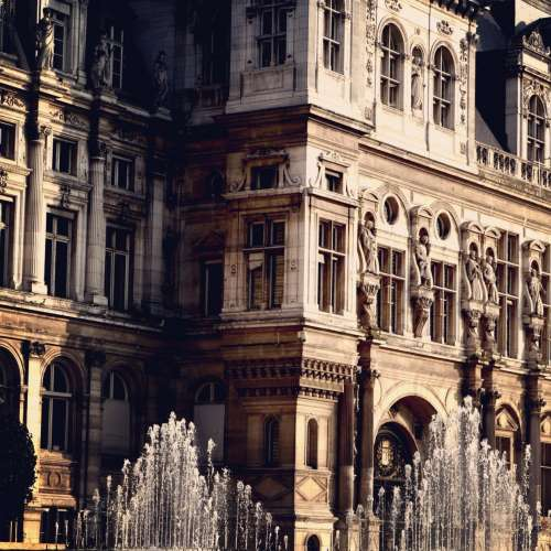 A Sun-Kissed Baroque Building OverLooking Water Fountains Photo