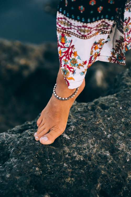 A Tanned Woman Exhibits Anklet On Rocky Seashore Photo