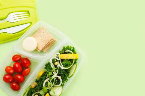 A Tupperware Lunch Box Separates Salad Ingredients Photo