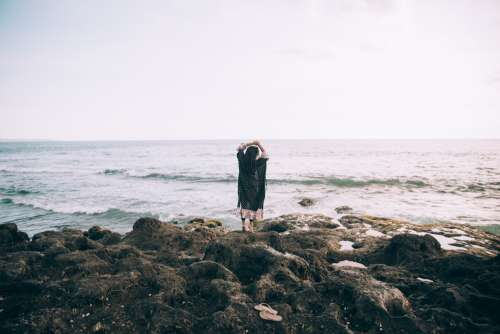 A Woman By The Beach Holds Her Hands Up In Reverie Photo