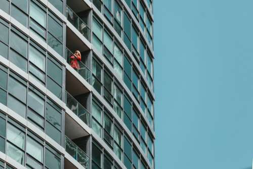 A Woman In A Red Jacket Inspects Her Phone On A Balcony Photo