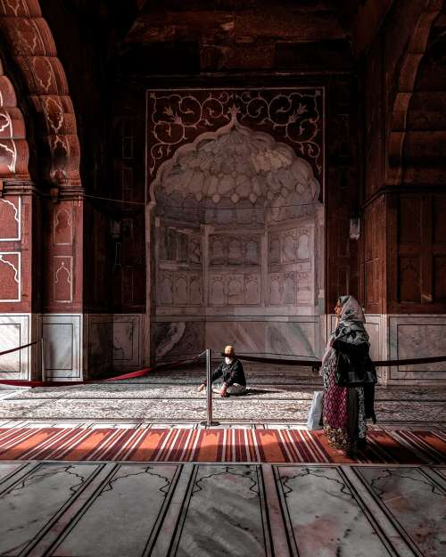 A Woman In Red Walks Through Arched Hall Photo