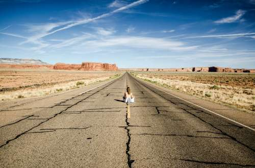 A Woman Sits In The Middle Of A Desert Highway Photo