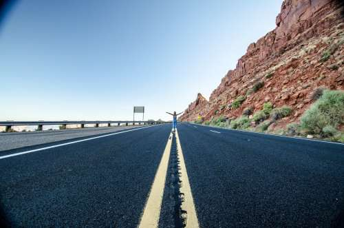 A Woman Stands In The Middle Of A Desert Highway Photo