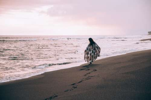 A Woman Walks Along The Beach Leaving Footprints In The Sand Photo