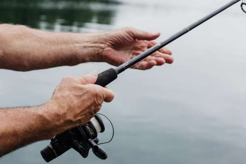 Aged Hands Hold A Fishing Rod Over Still Waters Photo