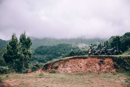 Group Of Touring Motorbikes Parked Along Jungle Roadway Photo