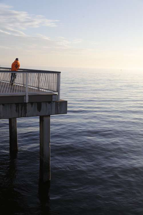 Lone Man Stands On A Pier At Sunset Photo