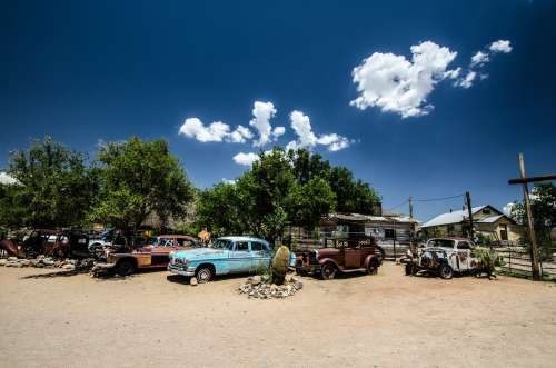 Old Rusty Cars Sit Under Trees In The Desert Photo
