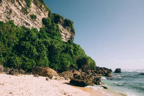 Sandy Beach Surrounded By Rocky Cliff And Jungle Photo