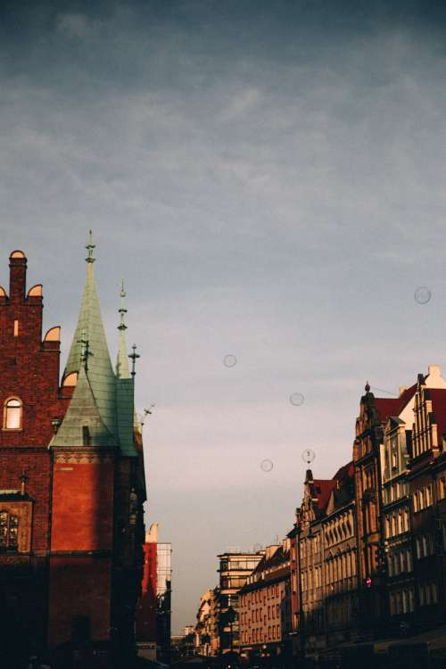 Soap Bubbles Float Over Red Brick Spires Of A Town Photo