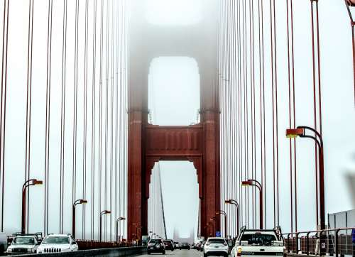 Traffic On A Suspension Bridge Suspended In Mist Photo
