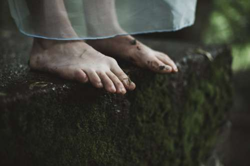 Two Dirty Feet On Mossy Ground Photo